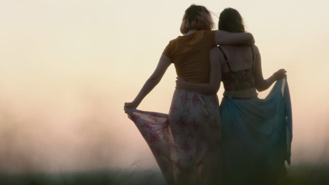 WS SLO MO. Sisters in flowing dresses stand with arms around one another in wheat field at sunset.