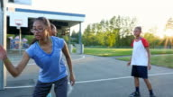 MS Sisters playing basketball on outdoor court on summer evening