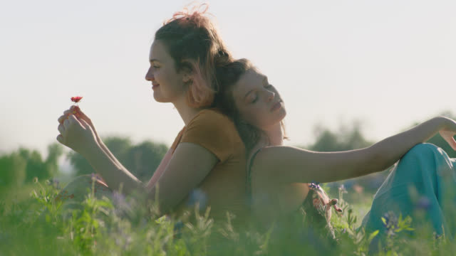 MS SLO MO. Sisters sit back to back in green field smelling wildflowers and daydreaming.