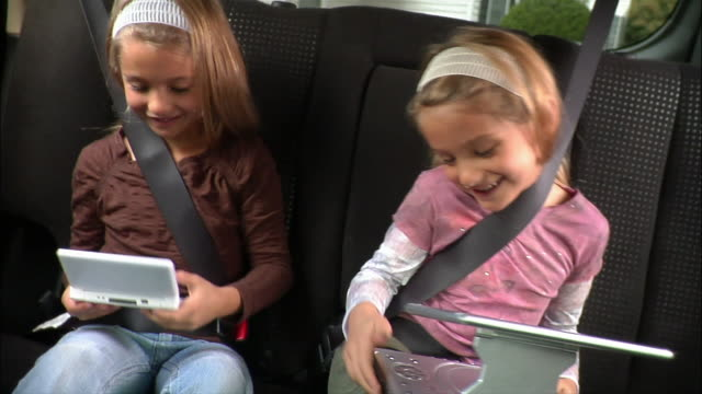 Sisters sitting in back seat of car playing video games / girl tickling twin sister