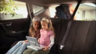 Sisters sitting in back seat of car watching movie together on portable DVD player while father loads trunk / mother fastens seat belt around girl
