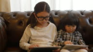 Sisters using tablet on sofa moving slider left to light