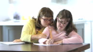 Sisters with down syndrome doing homework