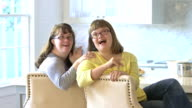 Sisters with down syndrome sitting in kitchen, talking