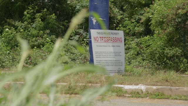 Six Flags in New Orleans abandoned since Katrina / sign still reads 'Closed for Storm' / over grown weeds and no trespassing signs