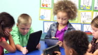 Six multi-ethnic children in schiool using digital tablets