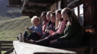 six people sitting on a bench, cottage, dolly shot, lateral
