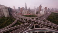 Six-level stack highway intersection with Shanghai Skyline from aerial position. Extreme wide shot.