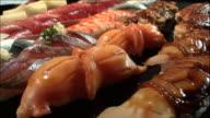 Sixteen varieties of nigiri ovals lie in rows.