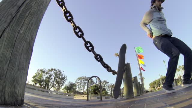Skateboarder doing an ollie over chains.