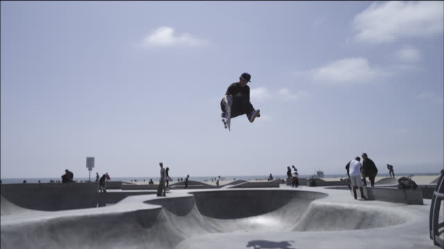 Skateboarder launches out of bowl, gets air, bails out of the trick in mid-air, tosses his board; beach and ocean in background, Venice Beach skate park.