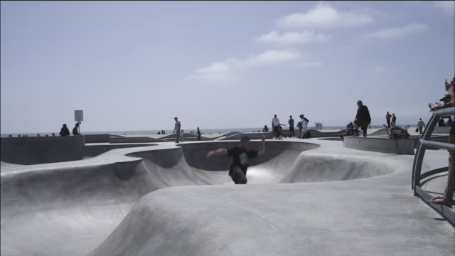 Skateboarder launches out of bowl, gets air, lands successfully; beach and ocean in background, Venice Beach skate park.