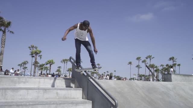 Skateboarder performs rail slide on stairway rail, falls off board on landing.