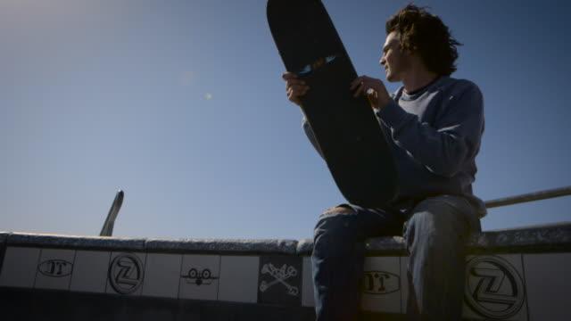 skater sitting at dog bowl waving at friends venice california skatepark