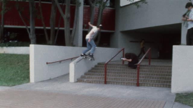 Skater sliding down handrail / falling off skateboard