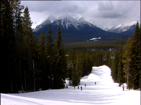 Ski slope lined with tall pine trees skiers jump over mogul at bottom of slope and cable cars zig zag overhead jagged snow dusted mountain in background Canada.