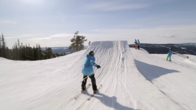 A skier doing a jumping trick on skis in the winter at a ski resort.