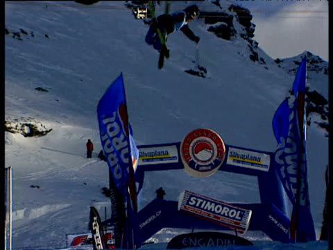 Skier flies off snow ramp and performs twists and turns in midair Engadin Mountain Corvatsch Switzerland