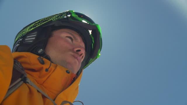 CU SLO MO Skier in yellow skiwear getting ready to ski / Alta, Snowbird, Utah, USA