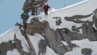 WS TD SLO MO Skier jumping off cliff and landing in powdery snow / Alta, Snowbird, Utah, USA