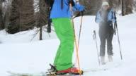 Skier kicks snow up onto companion, playfully