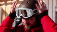 Skier putting on helmet and goggles
