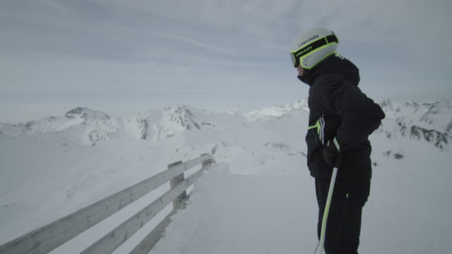 Skier standing on top of the mountain.
