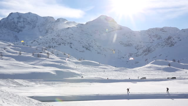 Skiers hike, and distant parasailers ski on fresh fallen snow
