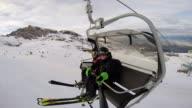 Skiers taking chairlift up the mountain at a ski resort.  - filmed in Kaprun, Austria, Europe