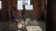 SLO MO. Skilled ballroom dancers perform synchronized routine by sunlit window in rustic barn.