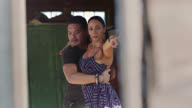 SLO MO. Skilled ballroom dancers twirl elegantly and pose for camera in mysterious rustic setting.