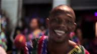 Skilled drummer in Brazilian samba line smiles at camera as he drums
