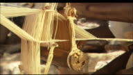 A skilled weaver threads a loom, Mali Available in HD.