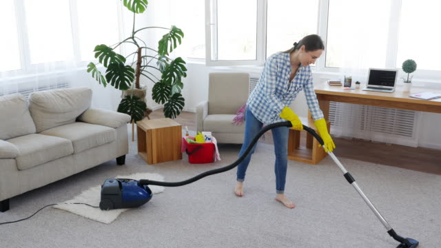 Skinny brunette cleaning with vacuum cleaner carpet