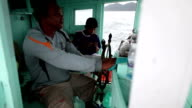 Skipper at the helm of a fishing boat in Thailand.