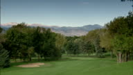 Sky TD WS First hole fairway sloping green lined w/ trees Rocky Mountains distant BG