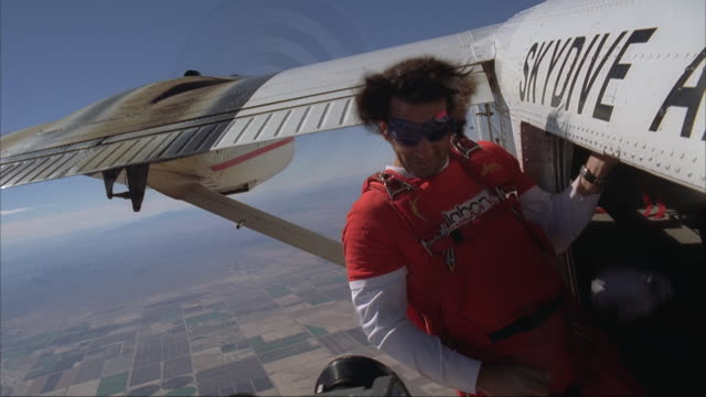 A skydiver and camera flyer exit the plane together.