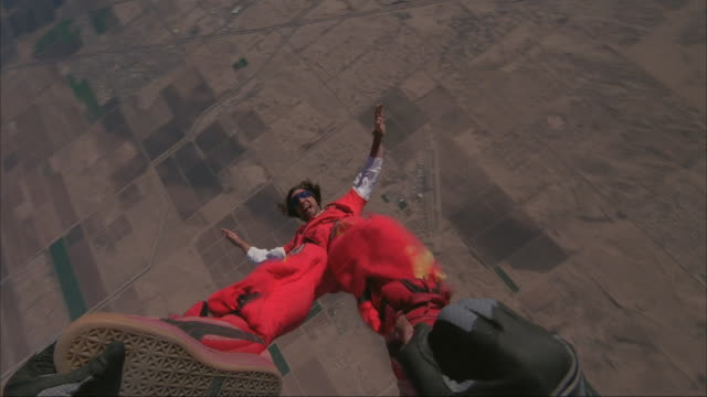 Skydiver exits plane with cameraman hanging onto his feet and does a series of spins.