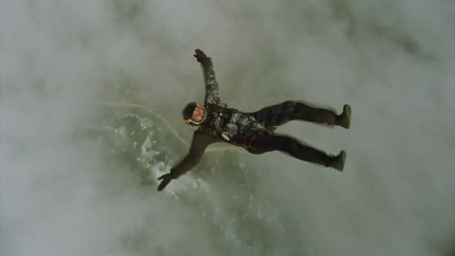 Skydiver flies over ocean and clouds