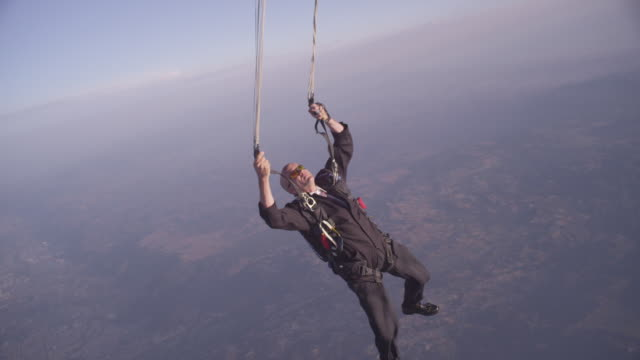 Skydiver in business suit looks up at malfunctioning parachute