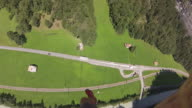 POV of skydiver landing in green field, alongside mountains