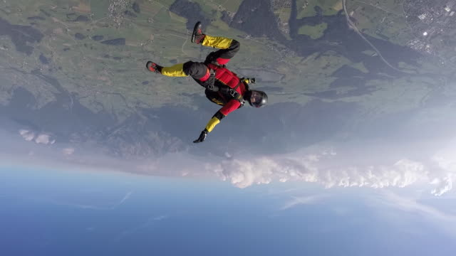 Skydiver performing acrobatics in free fall over alps