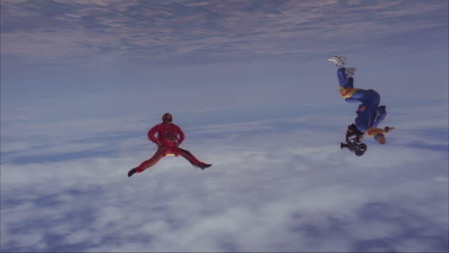 A skydiver spins headdown with a camera flyer filming him.