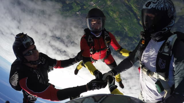Skydivers hold hands in freefall