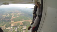 Skydivers leap from airplane towards distant fields