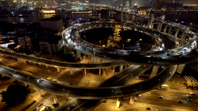 skyline and busy traffic on elevated road intersection at night, real time.