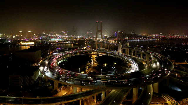 skyline and busy traffic on elevated road intersection at night, time lapse.