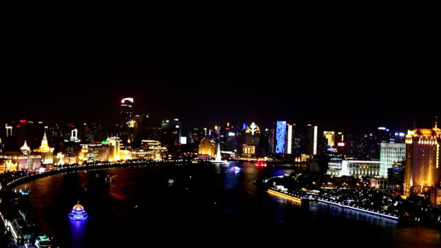 Skyline and modern buildings of shanghai at riverbank during night, real time.