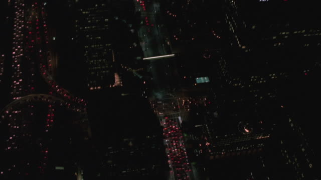 AERIAL Skyscrapers and city traffic at night / Los Angeles, California, United States