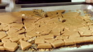 CU TU slab of freshly baked toffee broken into pieces with hammer by female worker in candy factory / Rancho Mirage, California, USA